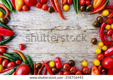 Frame of tomatoes and paprica family varieties over a rustic wooden background with copyspace - stock photo