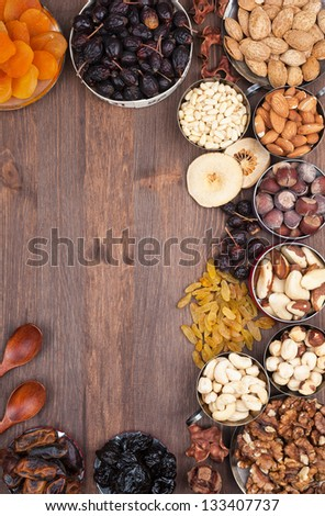 Frame of variety of fruits and nuts on a dark wooden surface - stock photo
