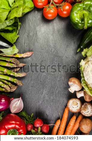 Frame or border of assorted farm fresh vegetables on slate with copyspace including carrots, asparagus, tomato, pepper, carrots , mushroom and radish - stock photo