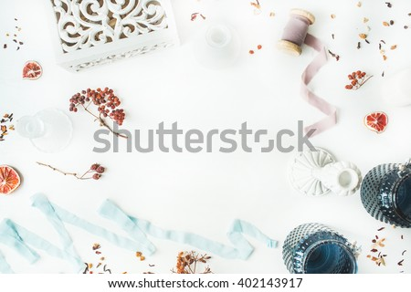 frame with candlesticks, blue ribbon, dry oranges and rowan branches isolated on white background. flat lay, overhead view - stock photo