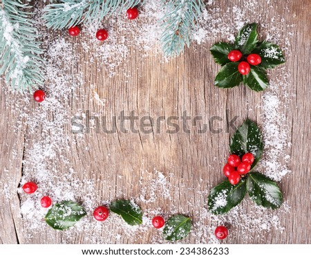 Frame with European Holly (Ilex aquifolium) with berries on wooden background - stock photo