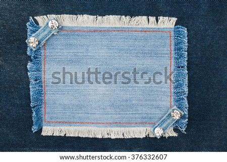 Frame with two straps jeans and rhinestones, lies on the dark denim, with space for your text - stock photo