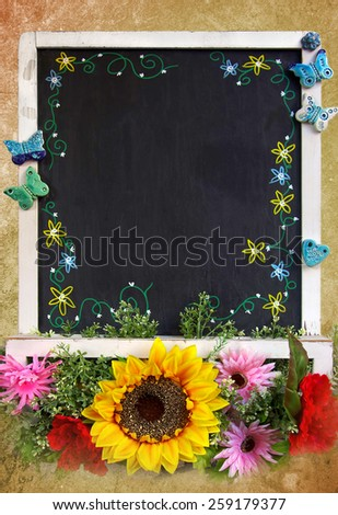 Framed blackboard with copyspace and decorated with colorful flowers - stock photo
