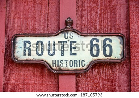 Framed sign for historic US Route 66 on a red building - stock photo