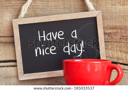 Framed vintage blackboard with a red cup of steamy coffee against wooden background with copy space with Have a nice day message - stock photo