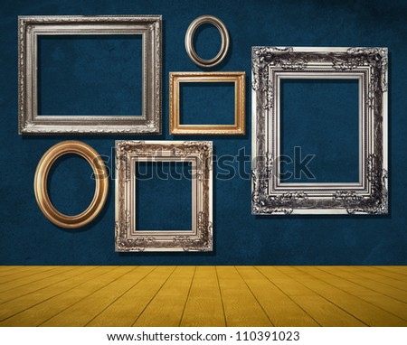 frames on grunge wall in room. - stock photo