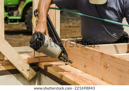 Framing building contractor framing up a wall section for a luxury custom house - stock photo