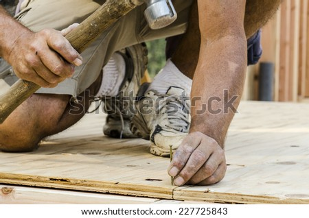Framing Contractor building in a window or door opening in outside bearing wood stud wall - stock photo