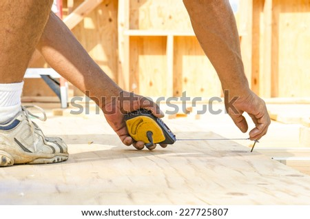 Framing contractor measuring and  chalk line to install plywood sub siding to wood joist - stock photo