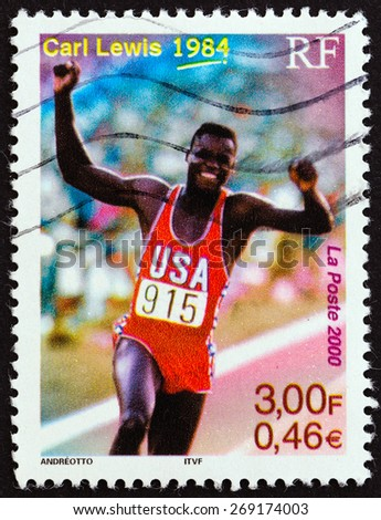 """FRANCE - CIRCA 2000: A stamp printed in France from the """"Sport Events of the 20th Century """" issue shows Carl Lewis (Olympic Gold medallist 100m, 200m, 100m relay and long jump, 1984), circa 2000. - stock photo"""