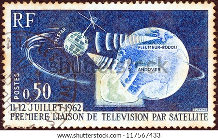 "FRANCE - CIRCA 1962: A stamp printed in France from the ""1st Transatlantic Telecommunications Satellite Link"" issue shows Telstar satellite, globe and television receiver, circa 1962. - stock photo"