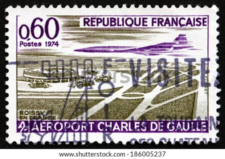 FRANCE - CIRCA 1974: a stamp printed in the France shows Concorde over Charles de Gaulle Airport, Paris, circa 1974 - stock photo