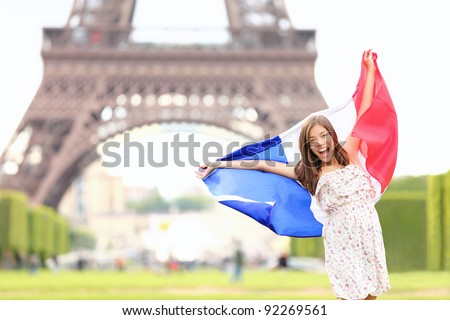 France - french flag woman by Eiffel tower, Paris. France travel concept with excited and happy young girl holding the French flag. - stock photo
