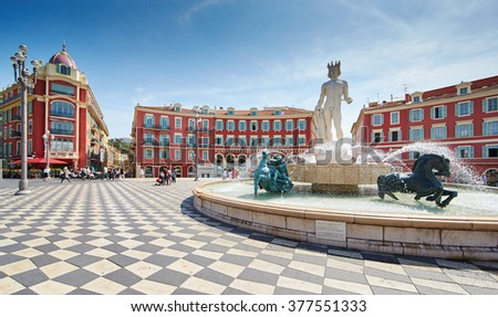 France, Nice, 08.09.2015: Fountain of the Sun, Place Massena in center of Nice, Plassa Carlou Aubert, tourism, sunny day, blue sky, square tiles laid out in a checkerboard pattern, Apollo statue - stock photo