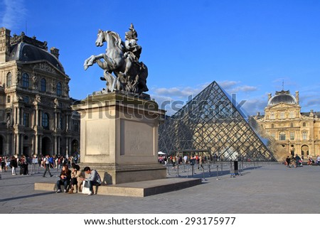 FRANCE. PARIS - JUNE 24, 2015: Tourists near the Louvre Museum and the glass pyramid. Louvre - the most famous museum in Paris. - stock photo