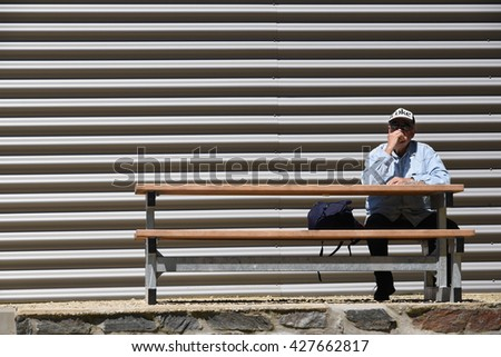 FRANCORCHAMPS, BELGIUM - MAY 5, 2016: Man with Coke cap, enjoying picnic sitting on a bench against a corrugated rear wall. Photo taken on circuit Spa-Francorchamps in Belgium. - stock photo