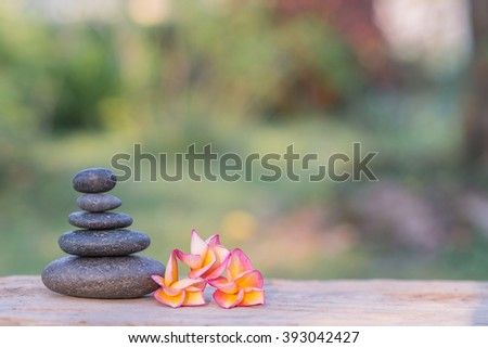 frangipani flower and stone zen spa on wood with garden blurred background - stock photo