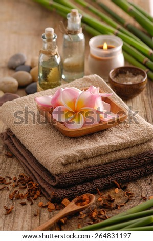 frangipani in bowl ,dry flower petals ,oil, towel, stones grove, on old wood  - stock photo