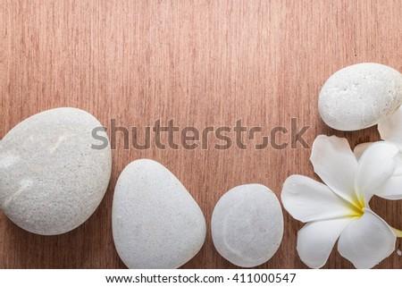 Frangipani or Plumeria  flower and stone zen spa on wooden plank - stock photo