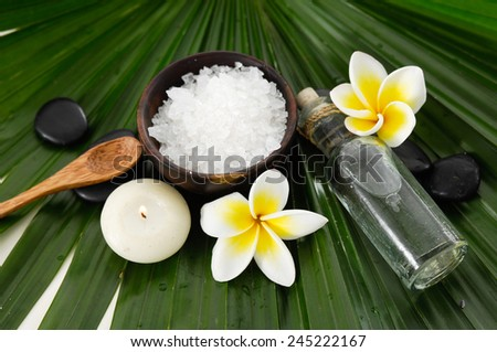 frangipani with candle with bowl of salt with spoon on green leaf - stock photo