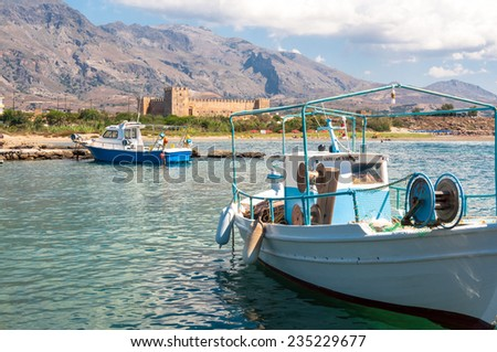 FRANGOKASTELLO, CRETE, GREECE - SEPTEMBER 15. Fishing boats in a small port in front of the venetian Fortress on September 15, 2014. Frangokastello is the known of his Castle and settlements on Crete - stock photo