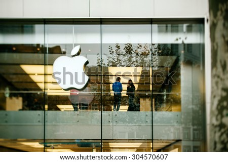 FRANKFURT AM MAIN, GERMANY - NOVEMBER 12, 2012: Apple Store logo and facade with Genius Employee explaining to a customer about the latest launched iPad Tablet. - stock photo