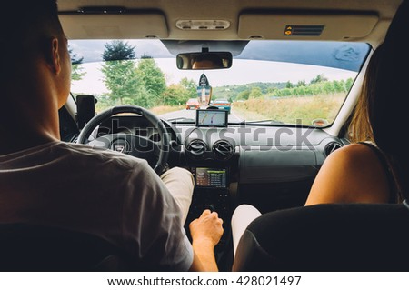 FRANKFURT, GERMANY- AUGUST 21, 2015 : Couple in a car , the man is driving , view from rear seat.  - stock photo