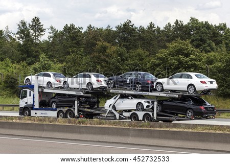 FRANKFURT, GERMANY - JULY 12, 2016: Car tranporter truck with new Mercedes Benz automobiles on the highway in Germany - stock photo