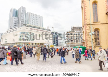 FRANKFURT, GERMANY - MARCH 1, 2014: People walking in the Hauptwache plaza in Frankfurt. The area is full of shopping district streets, including an underground pedestrian area, and several skycrapers - stock photo