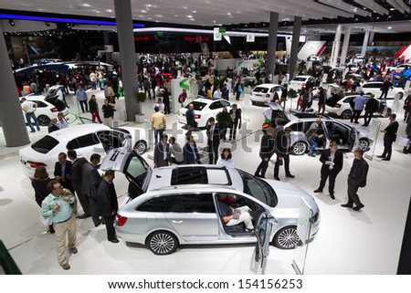 FRANKFURT, GERMANY - SEP 13: Visitors at the IAA motor show on Sep 13, 2013 in Frankfurt. More than 1.000 exhibitors from 35 countries are present at the world's largest motor show.  - stock photo