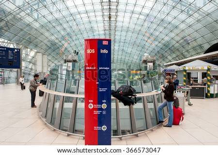 FRANKFURT, GERMANY - SEPTEMBER 14, 2009: Deutsche Bahn train station in Frankfurt Airport with people commuting and woman eating a german sandwish near glass wall.  - stock photo