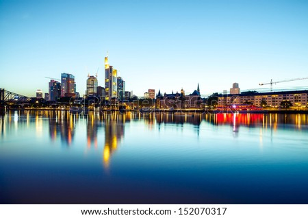 Frankfurt skyscrapers reflecting in the water at sunset - stock photo