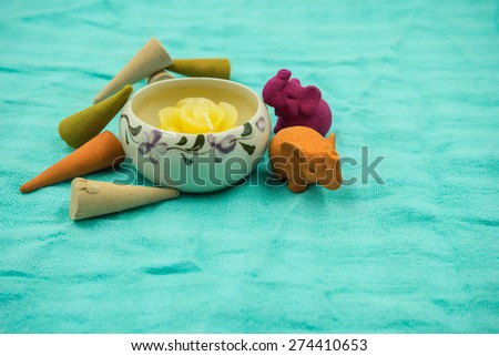 Frankincense and Scented candles on green background. - stock photo