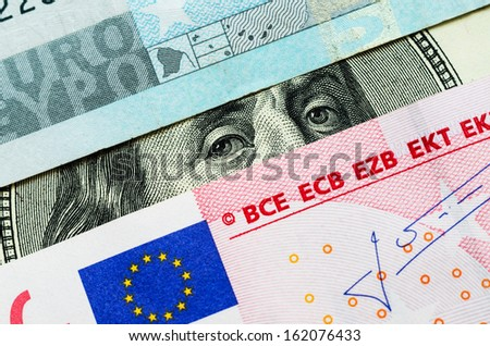 Franklin stare between euro banknotes. Close-up of one hundred dollar bill and European Union Euro note - stock photo