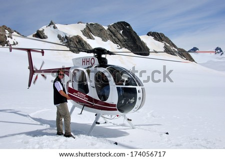 FRANZ JOSEF GLACIER, NEW ZEALAND: DECEMBER 24, 2009: Pilot welcomes passengers aboard his helicopter on the snow above Franz Josef Glacier, Westland, New Zealand - stock photo