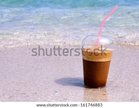 Frappe coffee in cup at the seaside.Selective focus on the coffee - stock photo