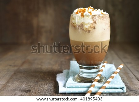 Frappuccino with caramel syrup and whipped cream in a glass on rustic background. - stock photo