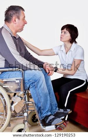 Frau spricht Mann im Rollstuhl Trost zu - stock photo