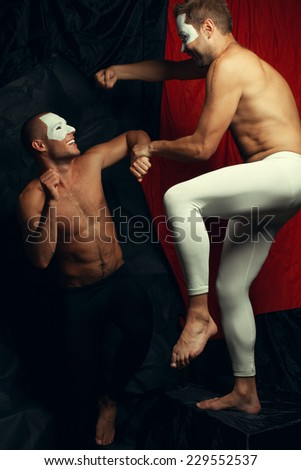 Freak circus concept. Two muscular mime artists, clowns with white masks on faces fighting and laughing over red cloth & black background. Vintage style. Studio shot - stock photo