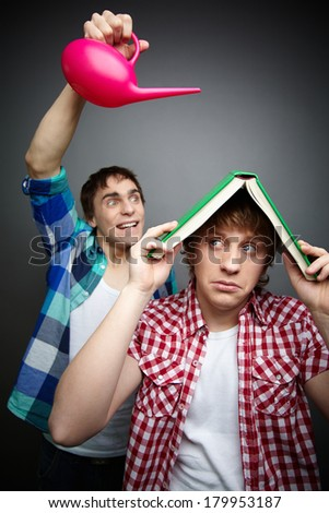 Freaky guy pouring water over his friend hiding under a book, fool�¢??s day celebration - stock photo