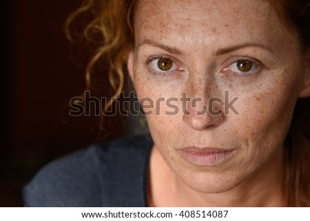 freckled young woman without make up close up - stock photo