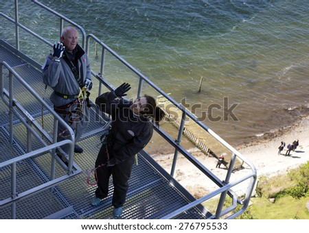 FREDERICIA, DENMARK -  MAY 10, 2015: Bridgewalking Littlebelt. Official opening day. Crown Princess Mary and Bridgewalkingchef, Knud Jeppesen on the bridge close to Jutland and beach. - stock photo