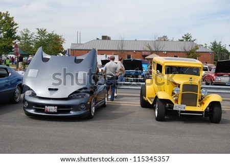 FREDERICK, MD- SEPTEMBER 16: Silver Sports Car, and a 1962 Yellow Ford Coupe on Sept. 16, 2012 in Frederick, MD USA. Alzheimer's Association Benefit Car Show at MVA in Maryland. - stock photo