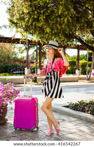 free beautiful fashionable hipster amazing redhead girl traveler in airport in the waiting area with a pink suitcase, camera, hat, stylish bright clothes, smiling, sport casual  - stock photo