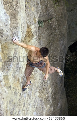 Free climber holding on the cliff, view from above - stock photo