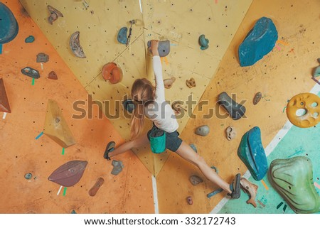 Free climber little girl practicing on artificial boulders in gym - stock photo