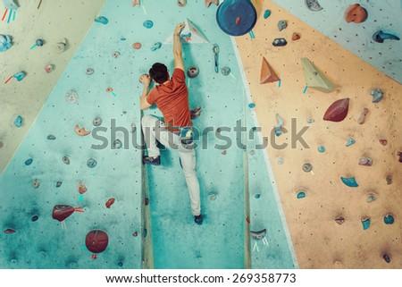 Free climber young man climbing artificial boulder indoors - stock photo