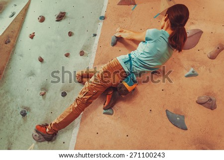 Free climber young woman climbing artificial boulder indoor. Focus on hands - stock photo