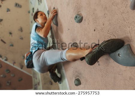 Free climber young woman climbing on practical wall indoor, bouldering - stock photo