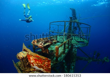 Free diver exploring the ship wreck in tropical clear sea - stock photo